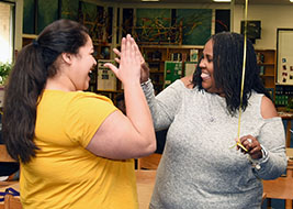 Two African American teachers high-five after learning they have won a grant.