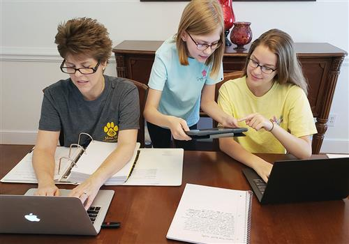 A mom and two daughters work at their dining room table with laptops.
