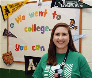 Female teacher poses in front of a bulletin board promoting college enrollment