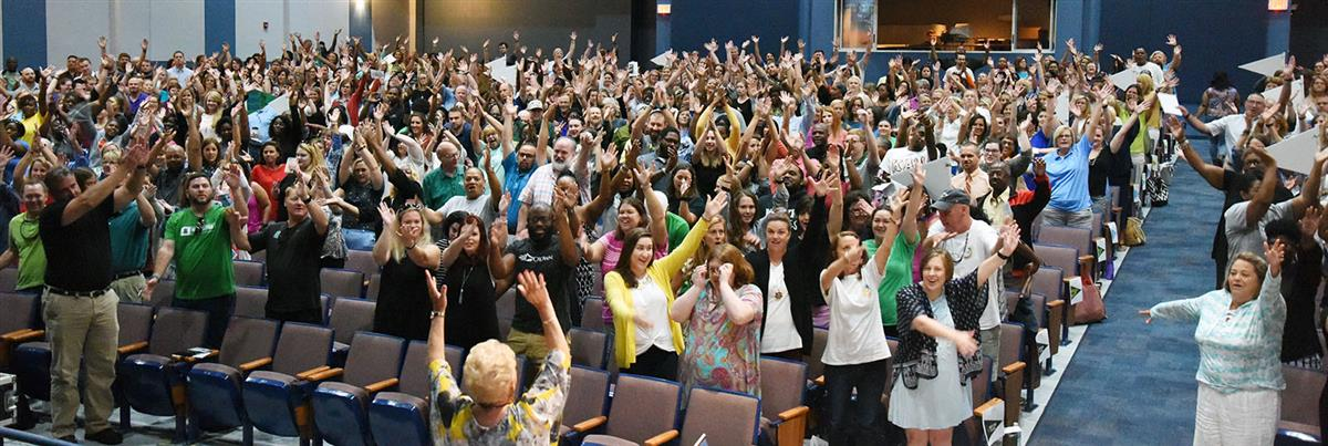 Teachers in a full auditorium wave their arms during an exercise.