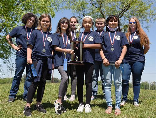 Six fifth graders, two in the center holding a trophy, are flanked by two female teachers.
