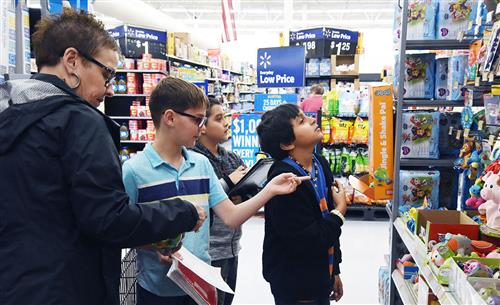 Three fifth grade boys shop at Walmart with the help of a female chaperone.