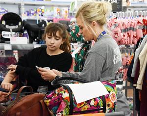 A female teacher and female student look at a handheld calculator while shopping at Walmart.