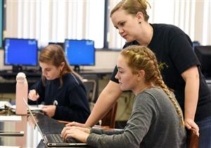 Female student works at laptop as female teacher leans over her to offer instruction.