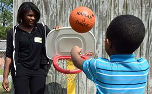 Female student watches as a boy of pre-kindergarten age tosses a basketball into a small goal.