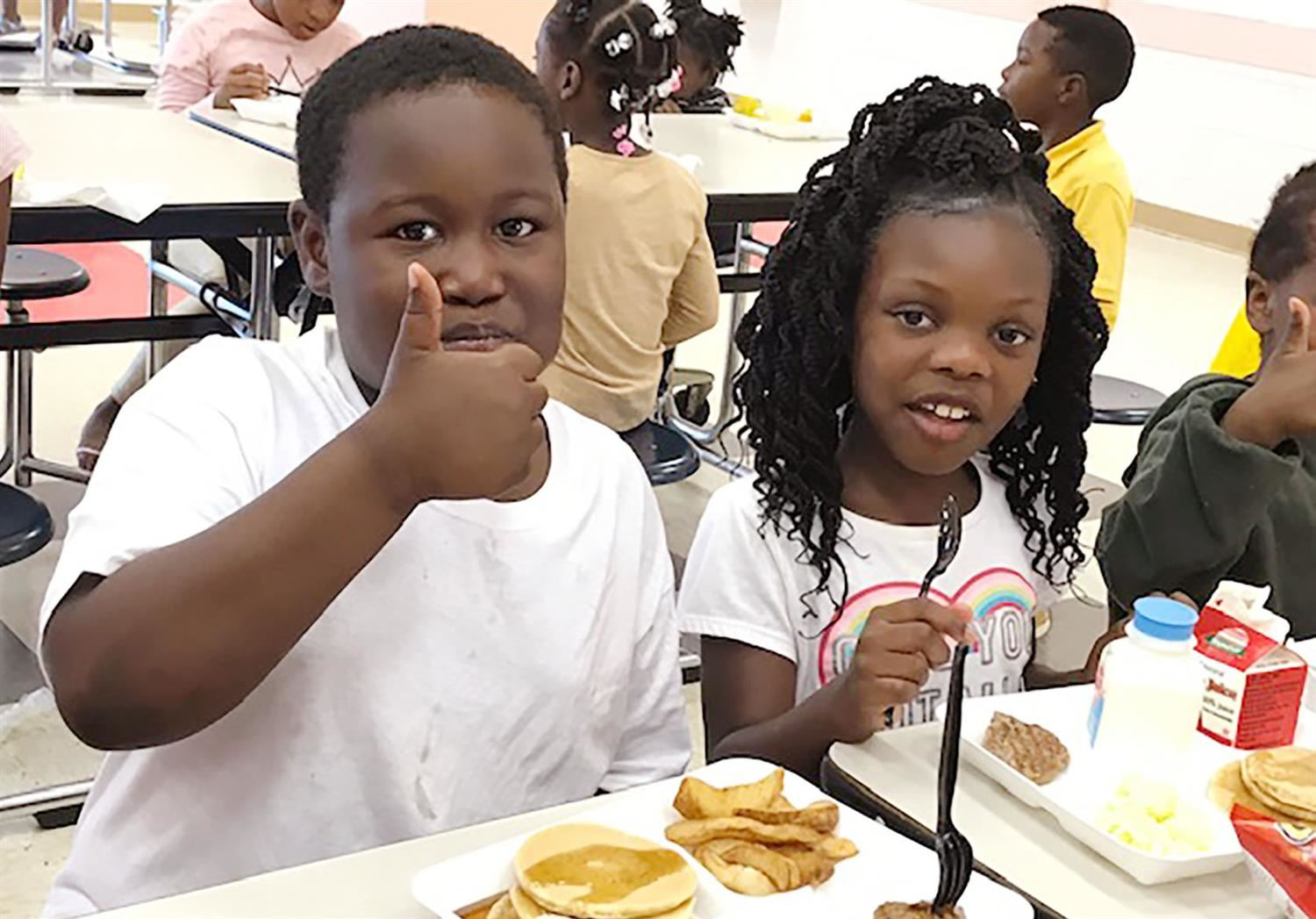 Elementary student gives a thumbs up while eating breakfast.