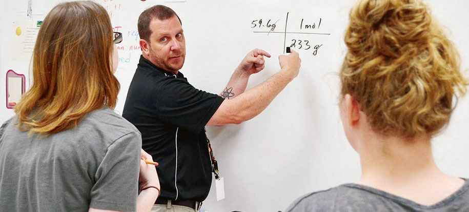High school science teacher at white board with two students