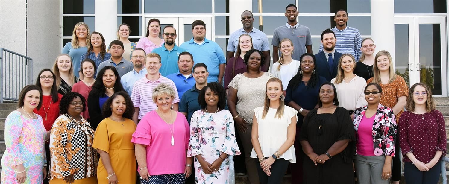 New teachers for 2019-2020 pose on steps of building.