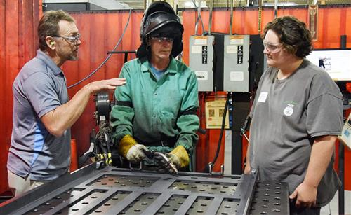 Welding student gets instruction at manufacturing plan