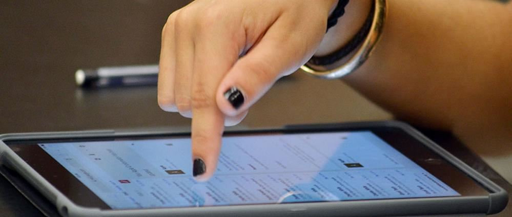 Student's hands hover above an iPad