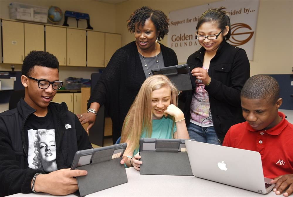 Middle school students with iPads work with teacher