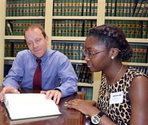 Student in law library with attorney looking at book